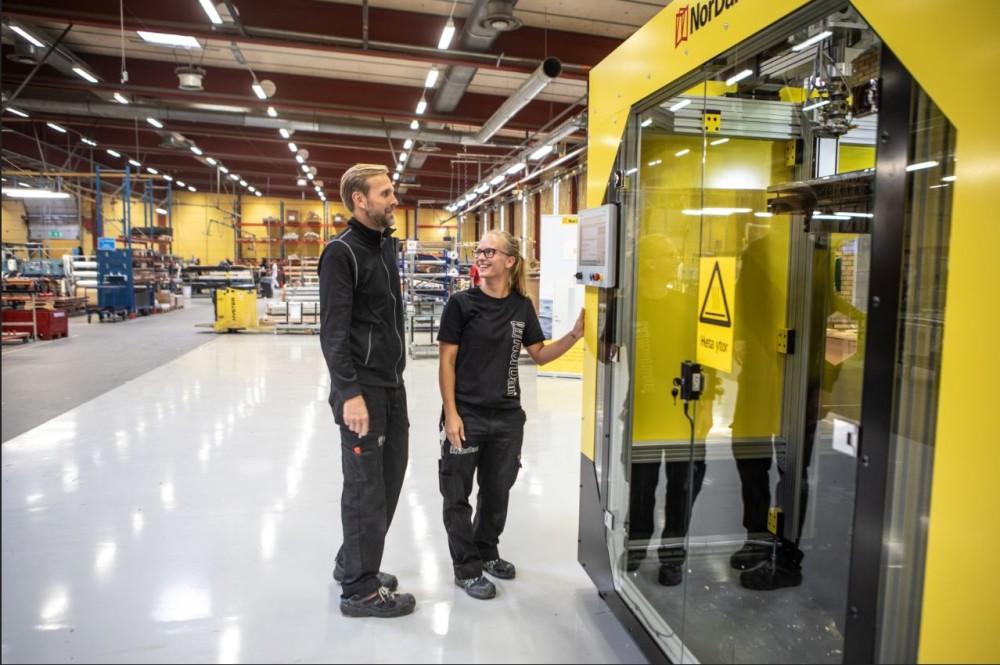 Medarbetare på NorDan framför 3d-skrivaren som tillverkar fönster och dörrar i hållbara material.