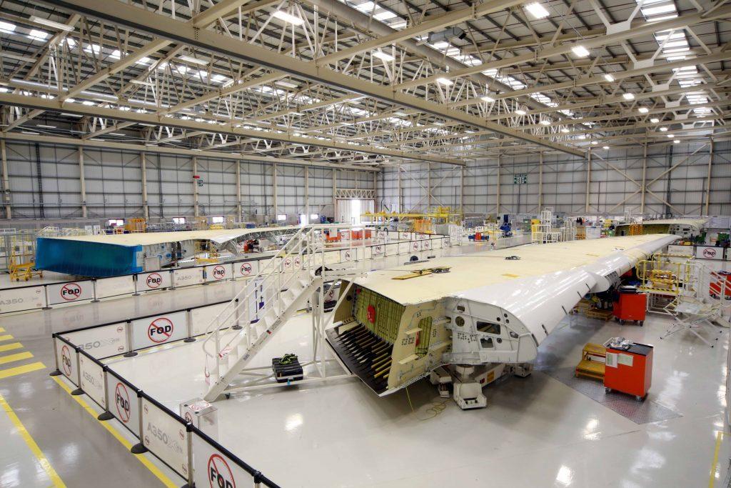 Bild inifrån Airbus fabrik där en flygplansvinge håller på att byggas.