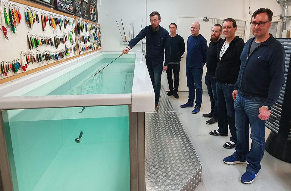 Fiskedragsdesignern Ismo Romppanen testar ett drag i testbassängen. Med på bilden är även Product Design Manager Mikko Rautiainen samt fiskedragskonstruktörerna Heikki Niemelä, Tero Holttinen, Jukka Vainio och Peter Mörsky.